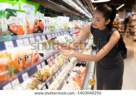 Mother Asian Working woman select pick up healthy nutrition food, yogurt milk from supermarket shelf rack after work. Concept decision Making choice select best thing for kid children family #1403040296