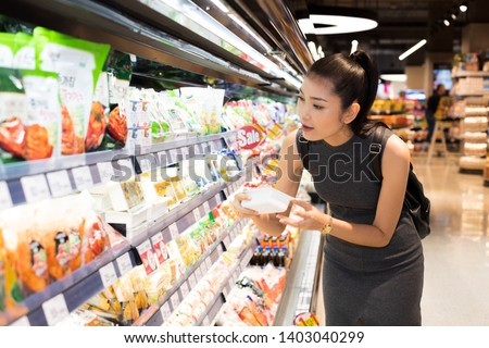 Mother Asian Working woman select pick up healthy nutrition food, yogurt milk from supermarket shelf rack after work. Concept decision Making choice select best thing for kid children family #1403040299