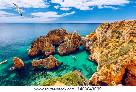 Panoramic view, Ponta da Piedade with seagulls flying over rocks near Lagos in Algarve, Portugal. Cliff rocks, seagulls and tourist boat on sea at Ponta da Piedade, Algarve region, Portugal.  #1403043095