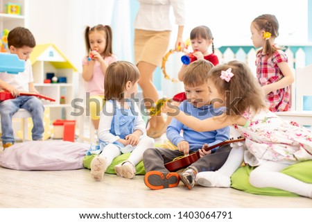 Group of kids playing with musical instruments in daycare #1403064791