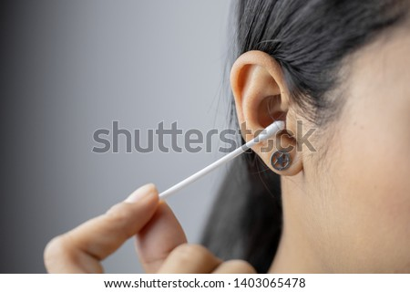 Concept of cleaning in the ear hole. Woman cleaning ear with cotton bud. #1403065478