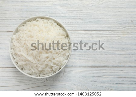 Bowl of tasty cooked rice on white wooden background, top view. Space for text #1403125052