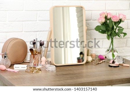 Different makeup products and accessories on dressing table in room interior