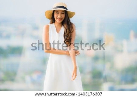 Portrait beautiful young asian woman happy smile relax on the roof top bar for leisure in holiday vacation #1403176307