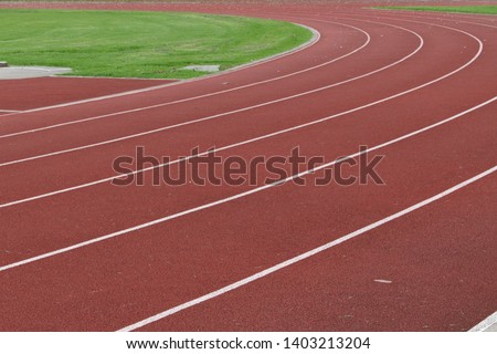 Curved section of red running race track with white lane markings ready for track and field events #1403213204