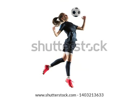 Young female football or soccer player with long hair in sportwear and boots kicking ball for the goal in jump isolated on white background. Concept of healthy lifestyle, professional sport, hobby. #1403213633