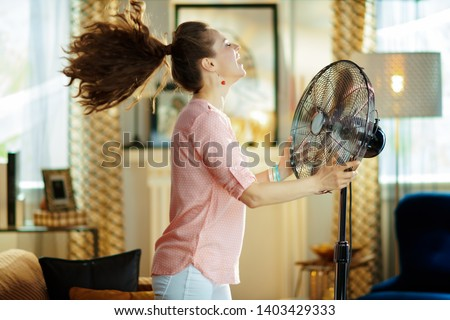 smiling modern housewife in the modern living room in sunny hot summer day enjoying fresh air in the front of working fan. #1403429333