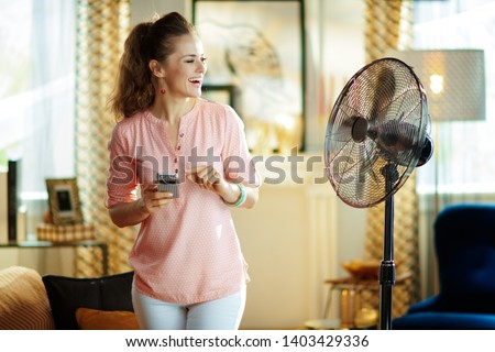 happy modern housewife in the modern house in sunny hot summer day using smart home app in smartphone to control fan. #1403429336