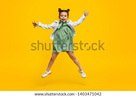 Full body cute kid in stylish dress swinging arms and smiling while jumping against bright yellow background #1403471042