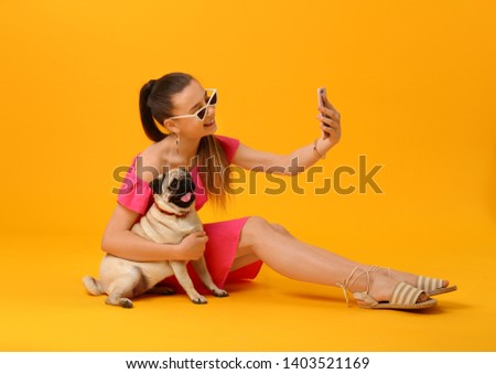 Teenage girl taking selfie with cute pug dog on color background