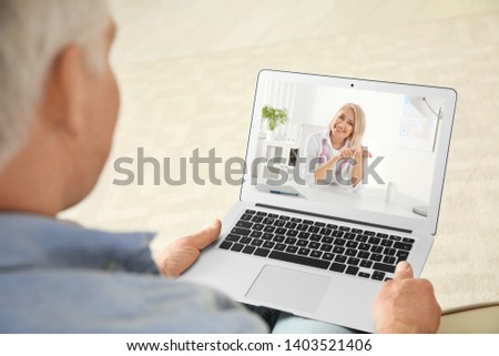 Man using laptop for online consultation with doctor via video chat at home, closeup #1403521406