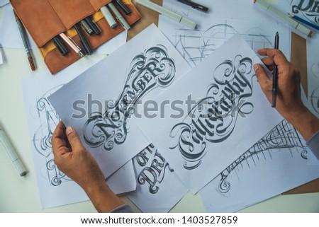 Typography Calligraphy artist designer drawing sketch writes letting spelled pen brush ink paper table artwork.Workplace design studio. #1403527859