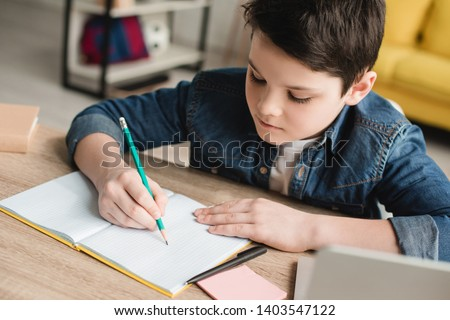 cute attentive boy writing in notebook while sitting at desk and doing homework #1403547122