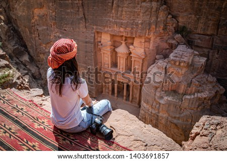 Asian woman traveler sitting on carpet viewpoint in Petra ancient city looking at the Treasury or Al-khazneh, famous travel destination of Jordan and one of seven wonders. UNESCO World Heritage site. #1403691857