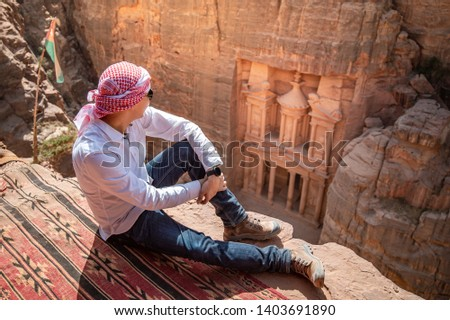 Asian man traveler sitting on carpet viewpoint in Petra ancient city looking at the Treasury or Al-khazneh, famous travel destination of Jordan and one of seven wonders. UNESCO World Heritage site. #1403691890