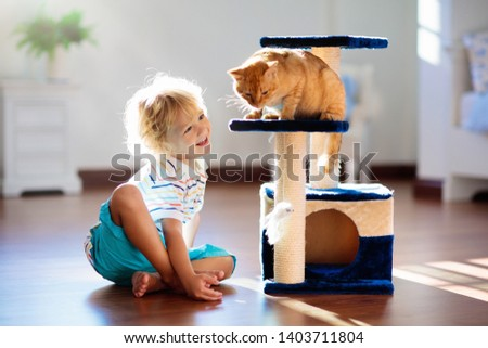 Child playing with cat at home. Kids and pets. Little boy feeding and petting cute ginger color cat. Cats tree and scratcher in living room interior. Children play and feed kitten. Home animals. #1403711804