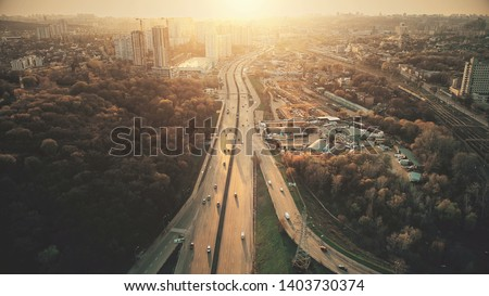 Urban Car Road Traffic Congestion Aerial View. City Street Motion Lane, Drive Navigation Overview. Busy Cityscape Speed Route with Forest Park Around. Travel Concept Drone Flight Shot Royalty-Free Stock Photo #1403730374