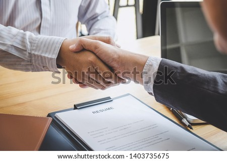 Greeting new colleagues, Handshake while job interviewing, male candidate shaking hands with Interviewer or employer after a job interview, employment and recruitment concept. Royalty-Free Stock Photo #1403735675