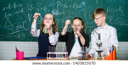 Group school pupils with test tubes study chemical liquids. Science concept. Girls and boy providing experiment with liquids. Test tubes with colorful liquid substances. Study of liquid states. #1403815070