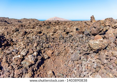 Unique panoramic view of spectacular melted lava river flows from a huge volcano. Hot black lava rocks, dried magma debris fields at Timanfaya National Park, Lanzarote, Canary Islands, Spain. #1403890838