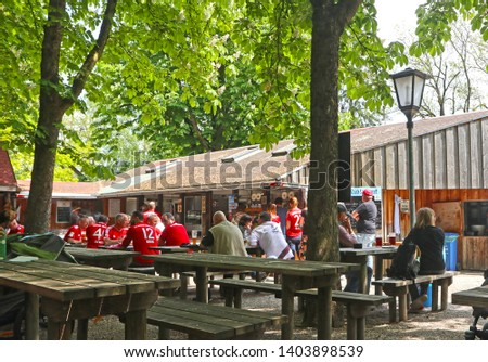 GARCHING, GERMANY - MAY 18, 2019 Fans of the FC Bayern wearing the t-shirt of the football club drink a beer at a typical beer garden before to go and watch the match of their favorite team #1403898539