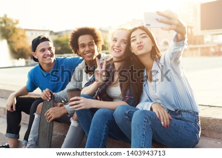 Group of multiethnic teenagers taking selfie, sitting on stairs outdoor, summer evening, sun flare #1403943713