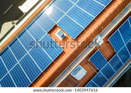 Aerial view of solar photo voltaic panels system on apartment building roof. Renewable ecological green energy production concept.