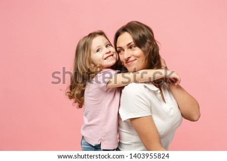 Woman in light clothes have fun with cute child baby girl. Mother, little kid daughter isolated on pastel pink wall background, studio portrait. Mother's Day love family, parenthood childhood concept #1403955824
