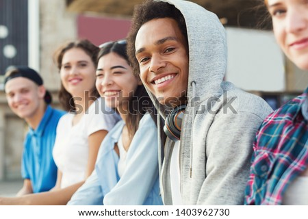 Multiethnic teen company spending time together, sitting outdoor, free space Royalty-Free Stock Photo #1403962730