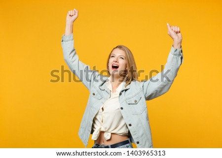 Portrait of happy young woman in denim casual clothes looking aside, doing winner gesture, saying Yes isolated on bright yellow orange wall background. People lifestyle concept. Mock up copy space #1403965313
