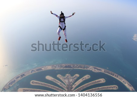 Dubai adventure sky fly.Adrenalin adventure flying in Skydive Dubai. Men in white suit fly above palm. Adventure background in the air #1404136556