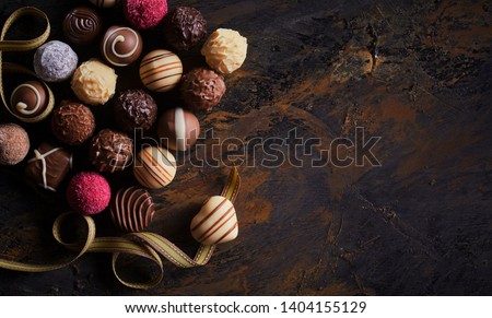 Rustic banner with luxury handmade chocolates and a heart shaped praline on a twirling gold ribbon over textured wood with vignette and copy space #1404155129