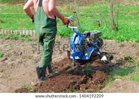 A farmer in rubber boots and overalls plowing the ground with a cultivator #1404192209