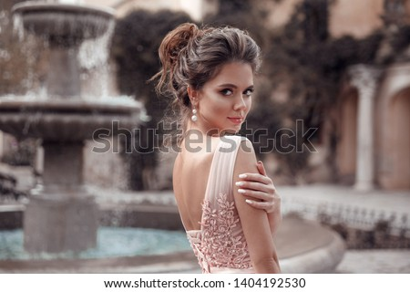 Beautiful bride with pearl earrings jewelry wears pink prom dress. Outdoor romantic portrait  of Attractive brunette woman with makeup and wedding  hair style posing at park. #1404192530