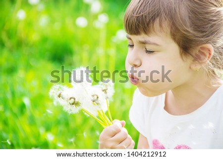 girl blowing dandelions in the air. selective focus. #1404212912