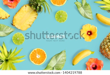 Creative layout made of pineapple, banana, orange fruit, lime and flowers on blue background.  Tropical flat lay. Summer fruits concept.  #1404219788
