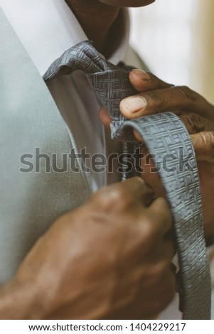 Black man fixing tie for wedding. #1404229217
