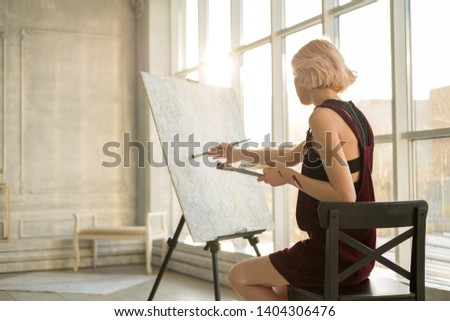 girl artist sitting in front of the easel in his bright and spacious Studio. slender blonde with short hair. white canvas, brushes and paints in the hands of the artist. paint strokes on the body #1404306476