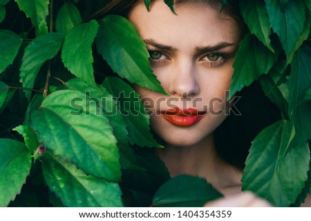 Green leaves bushes woman bright makeup close-up beautiful face                            #1404354359