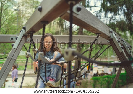 Cute girl having fan on playground Charming little brunette girl in jeans suit  #1404356252