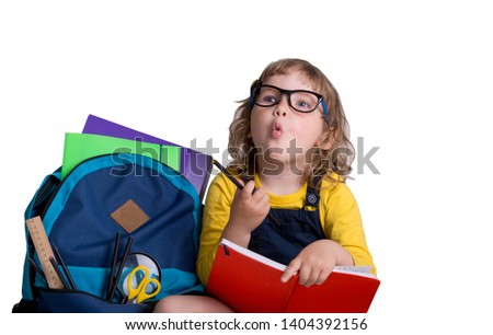 Back to school. Happy child girl with backpack and books pointing up. Pupil from primary school isolated on white background. Portrait of student in the classroom. Study process #1404392156