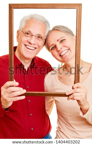 Happy seniors couple is looking together through an empty picture frame