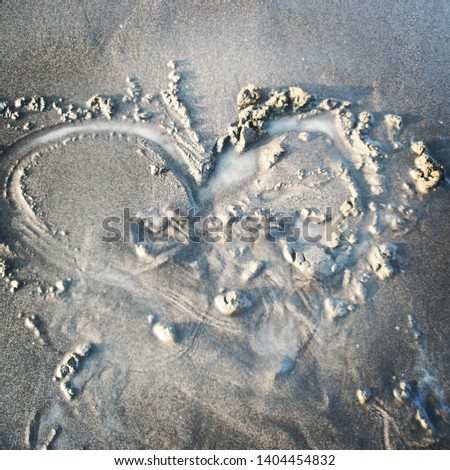Love sign writing on sand at the sunset time. A heart-shaped painting on a sandy beach. Heart drawn on hard wet sand,  empty space for text. #1404454832