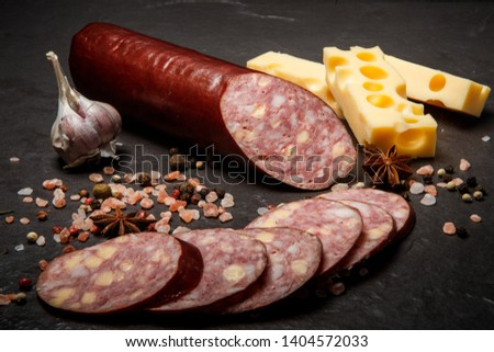 delicatessen sliced cheddar summer sausage with sliced pieces served with pink salt, spices, garlic, and hard cheese #1404572033
