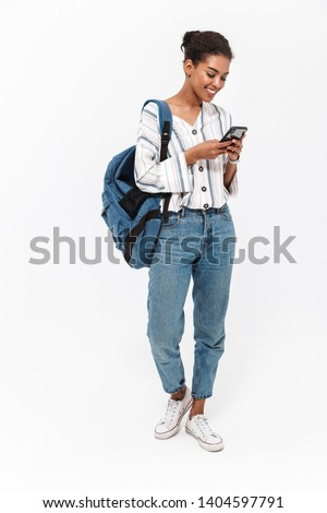 Full length of a portrait of an attractive young african woman carrying backpack standing isolated over white background, using mobile phone Royalty-Free Stock Photo #1404597791