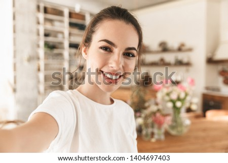 Image of nice charming woman wearing casual clothes taking selfie photo and smiling in cozy kitchen