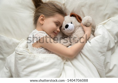 Smiling cute little girl hug teddy bear sleep peacefully in white bed relaxing on soft pillow, calm preschooler child enjoy daydream with plush toy taking nap under warm fluffy duvet at home