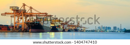 Panorama image of container cargo ship with ports crane bridge in harbor and refinery industrial at night logistics and transportation concept Royalty-Free Stock Photo #1404747410