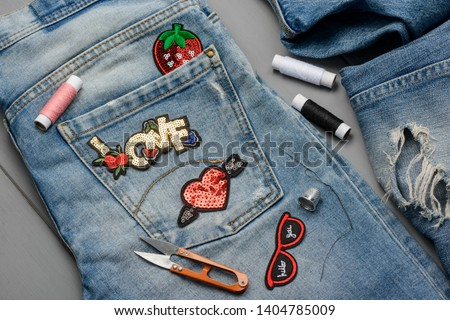 Applying patches to denim. Embroidered and sequin decorative elements to embellish worn jeans. DIY project concept. #1404785009