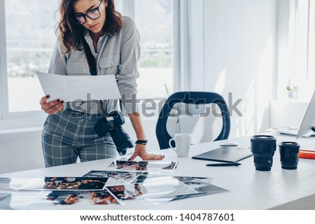 Young woman busy working in her studio. Caucasian female photographer checking prints after developing.